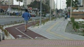 跑在沿城市街道的跑步的轨道的人 适合身体的活跃生活方式 股票录像