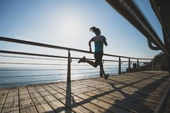 跑在海岸的健身妇女 库存照片