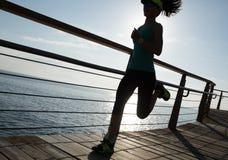 跑在海岸的健身妇女 免版税库存照片