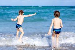 跑在海洋海滩的两个孩子男孩 获得的小孩乐趣 免版税图库摄影