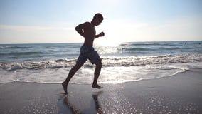 跑在海海滩的年轻运动的人在早晨 跑步沿海岸的运动人在一个晴天 男性运动员 股票视频