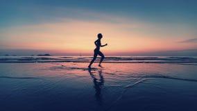 跑在海海滩的妇女被弄脏的剪影在黄昏 体育运动 库存图片