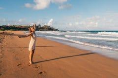 跑在海滩下的女孩在游泳随员 库存图片