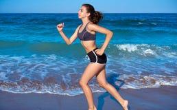 跑在海滩岸的青少年的女孩锻炼 免版税库存图片