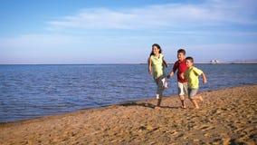 跑在海滩或红海,慢动作的三个孩子 股票录像