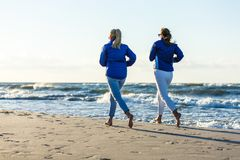 跑在海滩的中间年迈的妇女 免版税库存图片