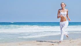 跑在海滩的健康妇女 免版税库存图片