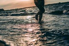 跑在海滩的女孩在日落 免版税库存图片