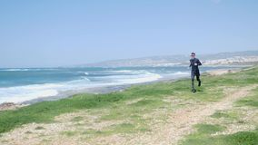 跑在海滩的年轻人适合的白种人人戴黑成套装备和太阳镜 波浪海在背景 影视素材