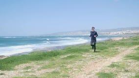 跑在海滩的年轻人适合的白种人人戴黑成套装备和太阳镜 波浪海在背景 t 股票录像