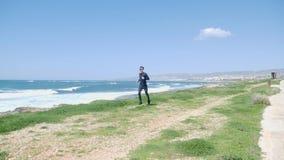 跑在海滩的年轻坚强的白种人人戴黑成套装备和太阳镜 沿海的足迹奔跑 影视素材