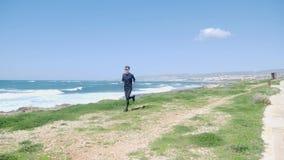 跑在海滩的年轻坚强的白种人人戴黑成套装备和太阳镜 沿海的足迹奔跑 t 影视素材