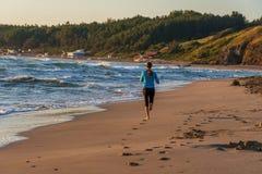 跑在海滩的年轻运动的女孩 免版税库存图片