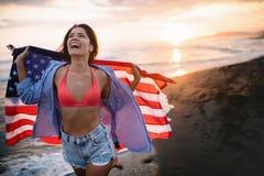 跑在海滩的愉快的妇女,当celebrateing独立日和享受自由在美国时 库存图片
