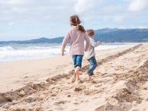 跑在海滩的愉快的孩子在度假 库存图片
