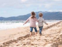 跑在海滩的愉快的孩子在度假 库存照片