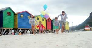 跑在海滩的愉快的家庭