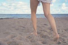 跑在海滩的沙子的妇女腿和费 免版税库存照片
