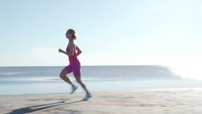 跑在海滩的独立年轻女人运动员在晴朗的海边背景中行使母赛跑者冲刺的训练 影视素材