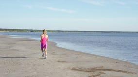 跑在海滩的独立年轻女人运动员在晴朗的海边背景中行使母赛跑者冲刺的训练 股票视频