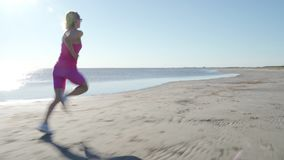 跑在海滩的独立年轻女人运动员在晴朗的海边背景中行使母赛跑者冲刺的训练 股票录像
