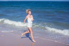 跑在海滩跳跃的愉快的美丽的自由的妇女嬉戏 免版税库存照片