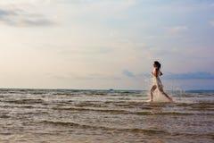 跑在海的美丽的妇女 免版税库存图片