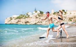 跑在海的年轻夫妇靠岸在日落 免版税库存照片