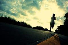 跑在海边路的赛跑者运动员 免版税库存照片
