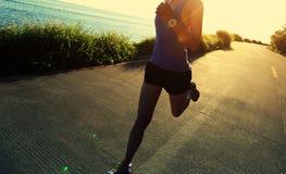 跑在海边路的赛跑者运动员 免版税库存图片
