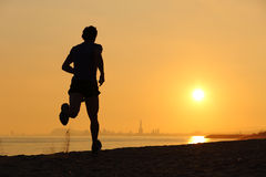 跑在海滩的一个人的背后照明在日落 免版税库存照片