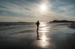跑在海滩的一个人 免版税库存图片