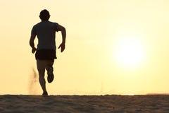 跑在海滩的一个赛跑者人的后面看法剪影 库存图片