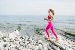 跑在海滩的亭亭玉立的健身女孩 机体理想的妇女 图库摄影