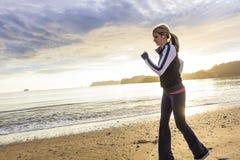 跑在海滩的健身妇女在日出 免版税库存图片