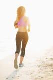 跑在海滩的健身少妇 库存照片