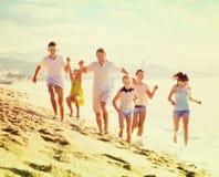 跑在海滩的大家庭 图库摄影