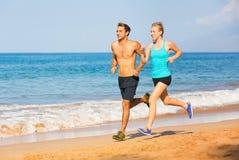 跑在海滩的夫妇 库存照片