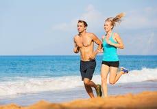 跑在海滩的夫妇 免版税库存图片