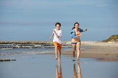 跑在海滩的女孩和男孩 免版税库存照片