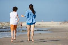 跑在海滩的女孩和男孩 免版税库存图片