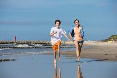跑在海滩的女孩和男孩 库存照片