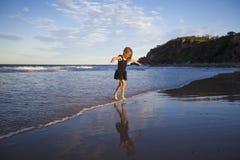 跑在海滩的女孩 库存图片