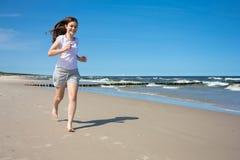 跑在海滩的女孩 免版税库存照片