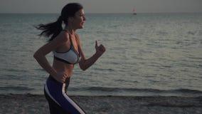 跑在海滩的女运动员的画象在日落 20s跑在海滩的沙子的女孩在日落 遗弃情人的 影视素材