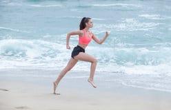 跑在海滩的妇女在多云早晨,侧视图 免版税图库摄影
