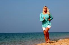 跑在海滩的妇女 免版税库存图片