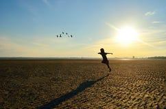 跑在海滩的孩子剪影 库存图片
