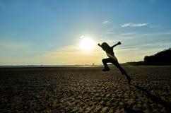跑在海滩的孩子剪影 免版税库存照片