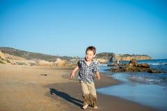 跑在海滩的小男孩 免版税库存图片
